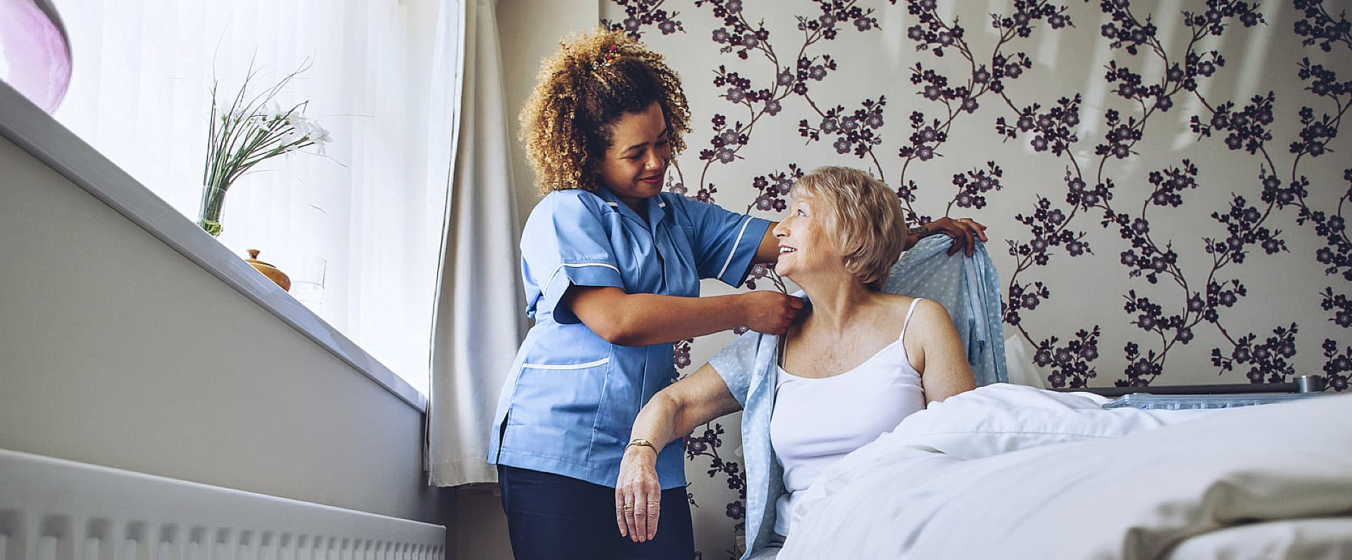 caregiver helping senior woman to change clothes