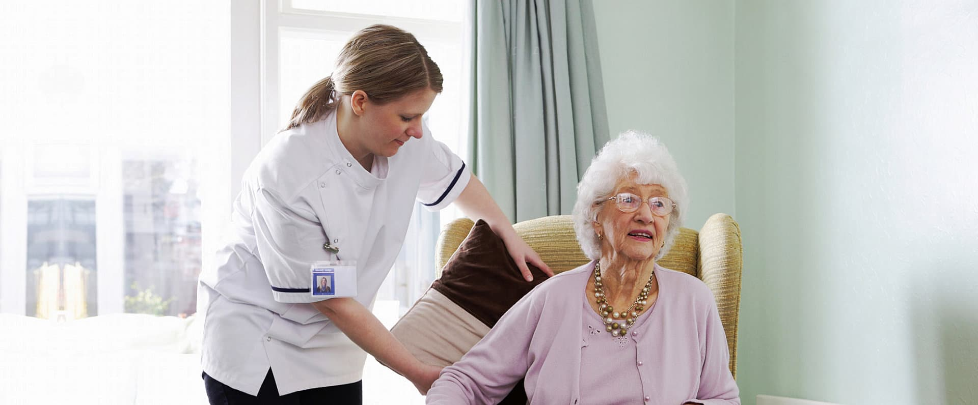 caregiver helping senior woman to sit