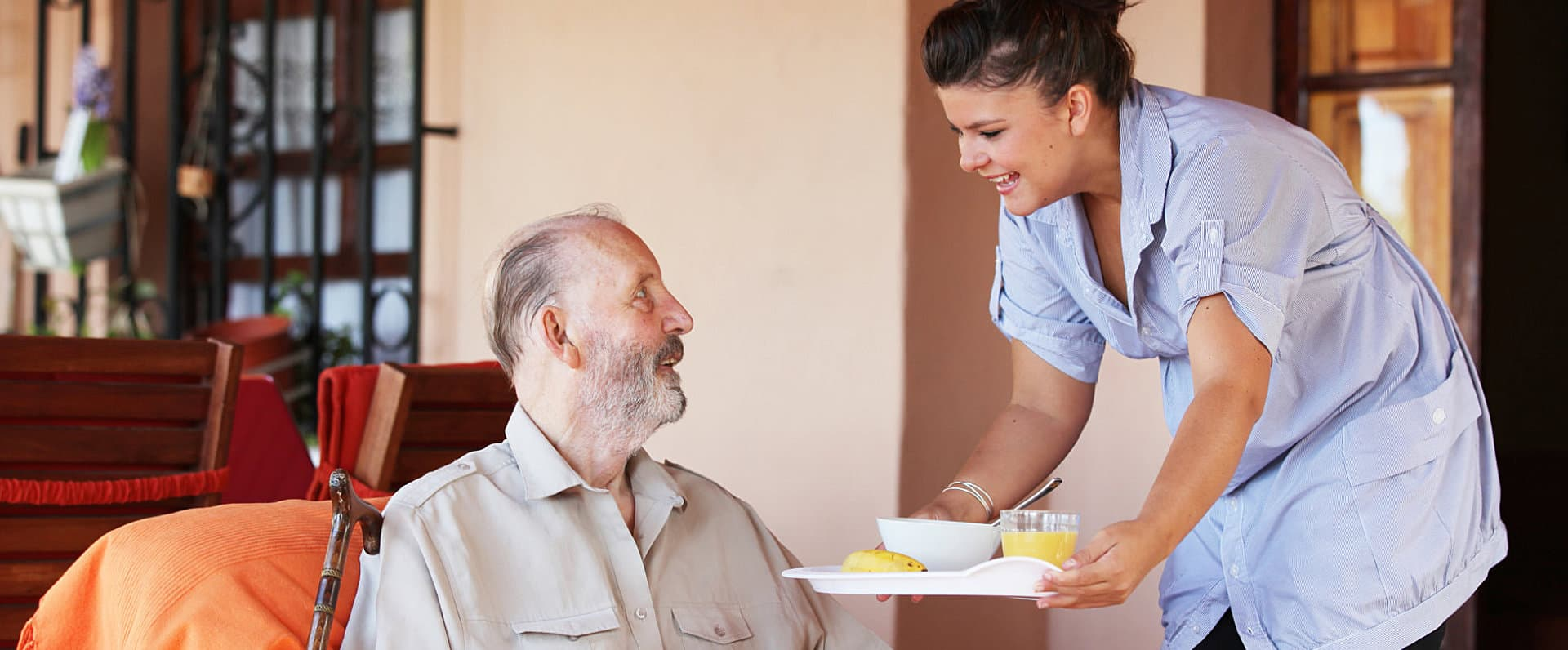 caregiver preparing food for senior man