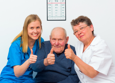 happy moments at the nursing home and elderly men showing thumbs up with his caregivers