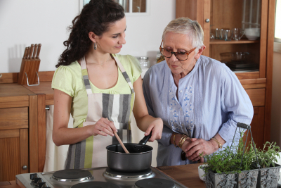 senior woman and a caregiver are cooking