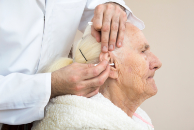 caregiver is cleaning the ears of an old woman