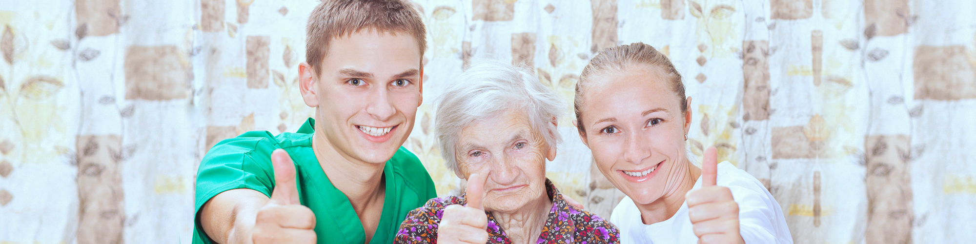 caregivers and senior woman showing thumbs up